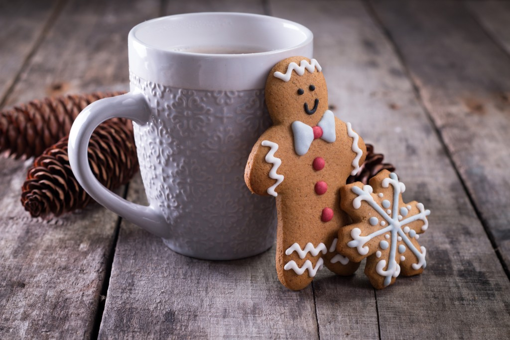 Cup of hot chocolate or cocoa with gingerbread cookie christmas composition on vintage wooden table background.